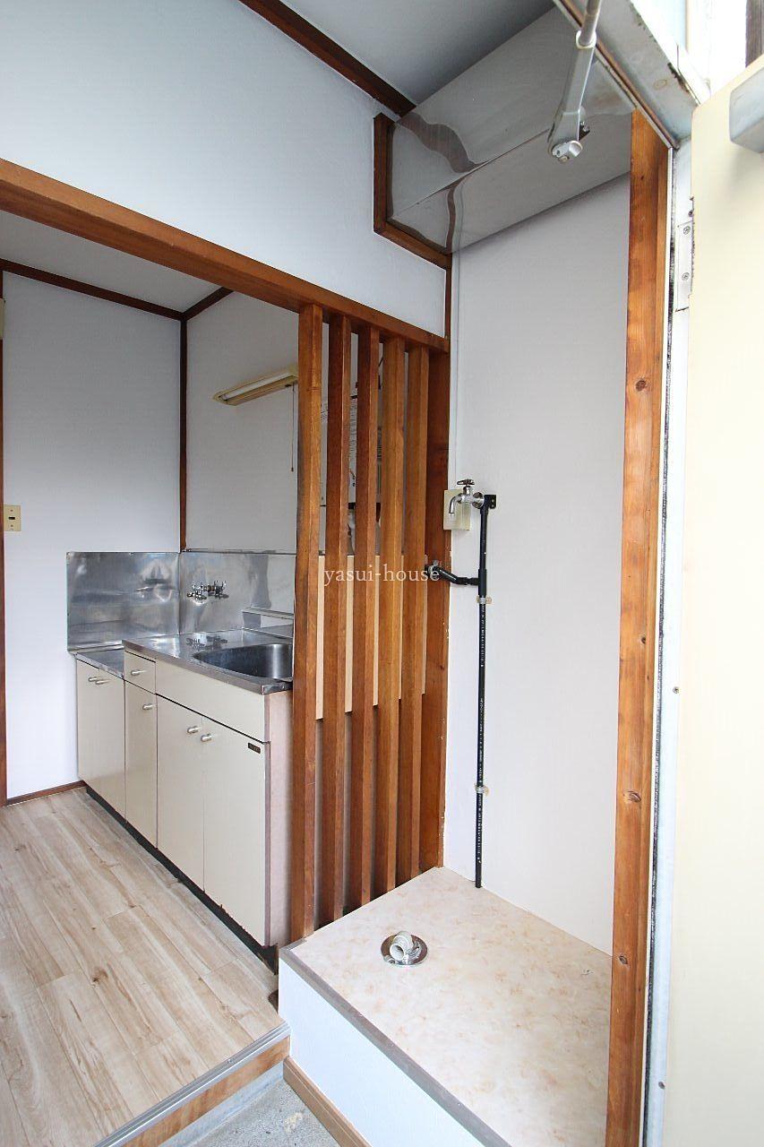 玄関の横に洗濯機置き場。流し台との境はくり棒で目隠し⁉